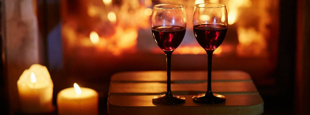 a couple of glasses of red wine set on a stool near lit candles and a fireplace b