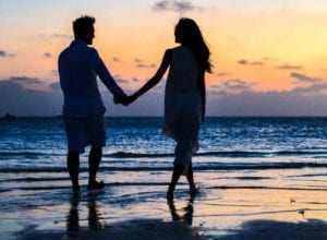 man and woman holding hands walking on seashore during 1024960 e1573582404165